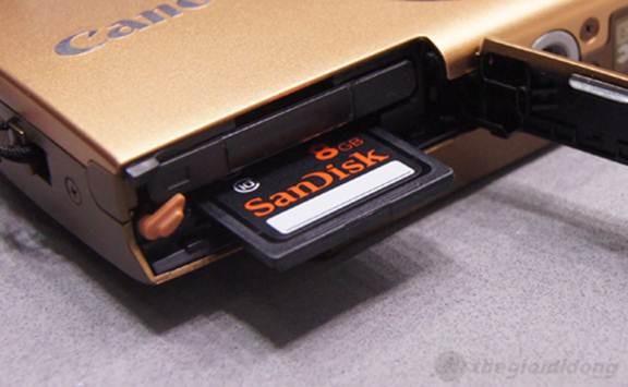 Cạnh dưới máy là khoang chứa pin sạc Li-ion Battery NB-11L và  khe cắm mở rộng hỗ trợ thẻ nhớ SD, SDHC và SDXC